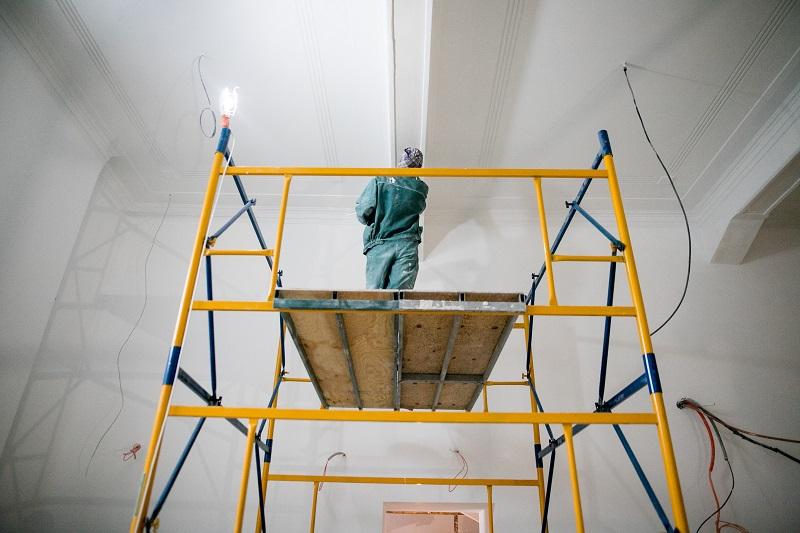 Robotnik stojący na rusztowaniu i malujący sufit